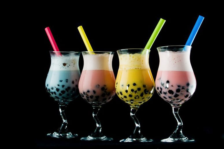 assorted flavors of bubble tea with straws