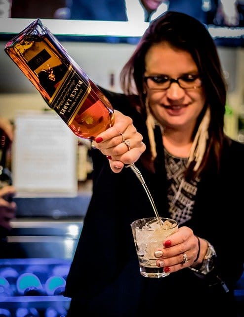 Female bartender pouring Johnnie Walker Black Label into glass with ice.